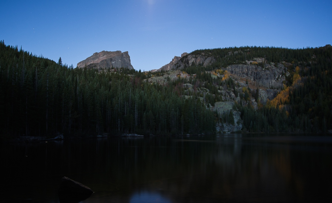 Bear Lake, in Rocky Mountain National Park lit b the moon (center to of frame), and the first rays of sunlight at the point of Astronomical sunrise.
