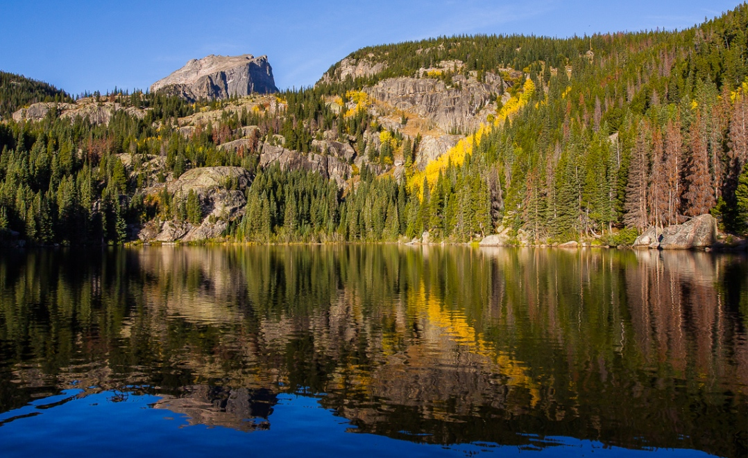 Hallette Peak and Fall-shrouded scenery reflected in the clear, cold water of Bear Lake at sunrise.