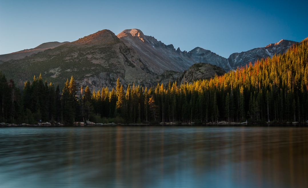 First light during early morning sunrise over Longs Peak, Rocky Mountain National Park. The peak and the forrest surrounding it are reflected as a rainbow spectrum in the throng if light ripples on the surface of Bear Lake.