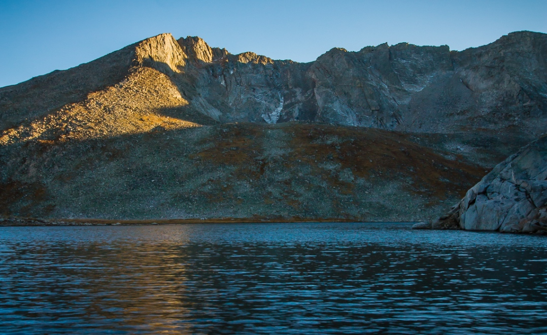 Mount Evans lit by the last few minutes of sunlight, reflected in the deep, dark blue waters of Summit Lake.