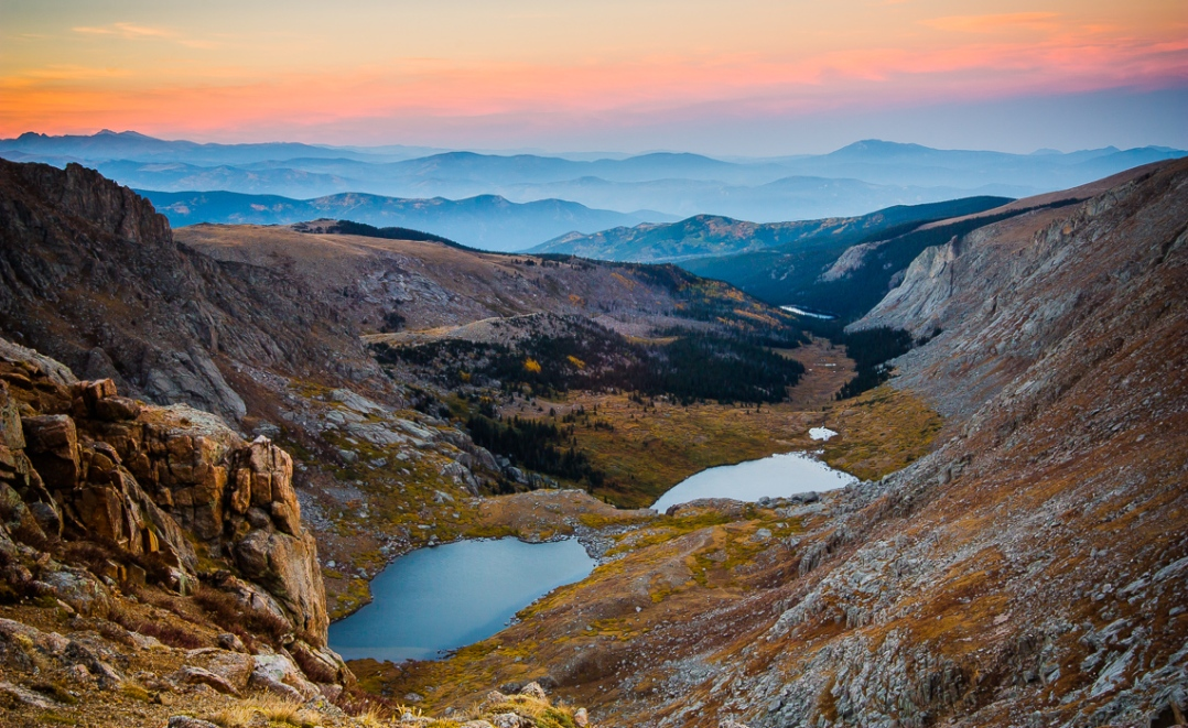 A vista of the Rocky Mountains, looking north from a rich near Summit Lake at Mount Evans. Smoke from wildfires raging in Boulder, CO shrouds the mountains as it drifts through the valleys, leaving only their peaks visible.