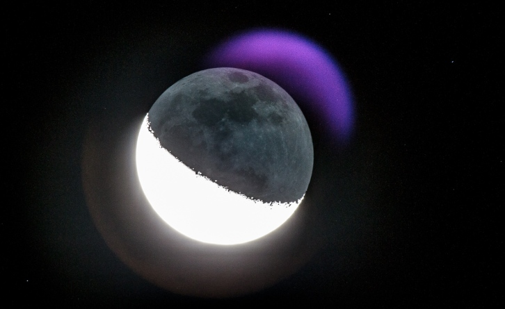 "The moon, exposed to capture the dark part, resulting in a purplish crescent ""moon flare"" ."